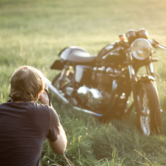 """Young man observing motorcycle"" stock image"
