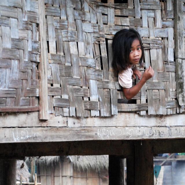 """Girl Peeking from tribal hut"" stock image"