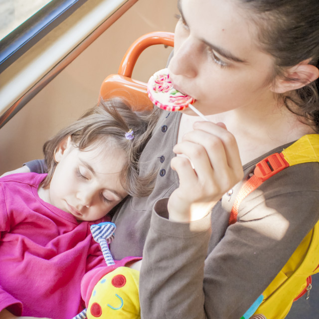 """Mother Holding Sleeping Toddler Eating Lollipop"" stock image"