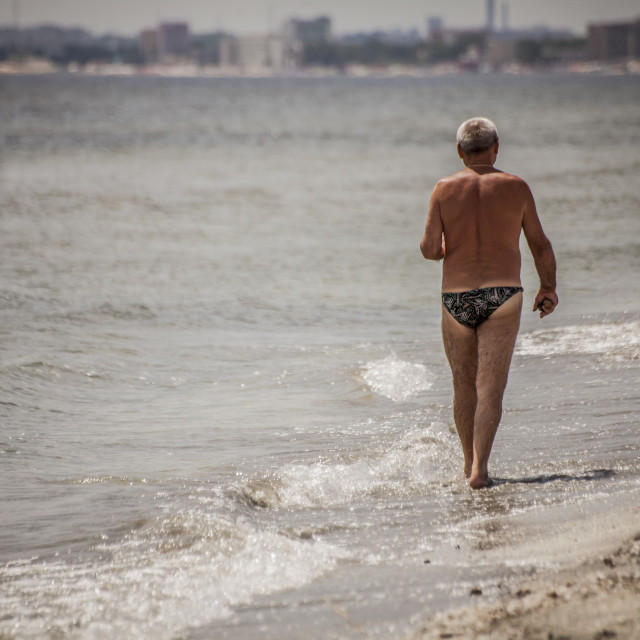 """Alone Senior Man Walking Down the Beach"" stock image"