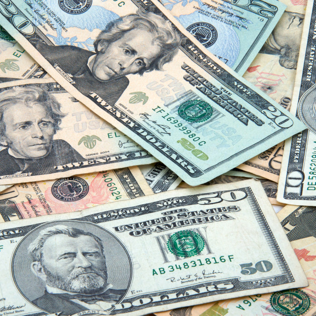 """""""$10, $20, and $50 bills scattered in a pile"""" stock image"""