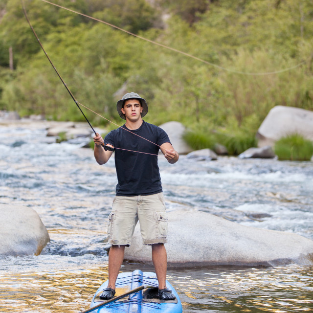"""A Fisherman on A Paddle Board"" stock image"