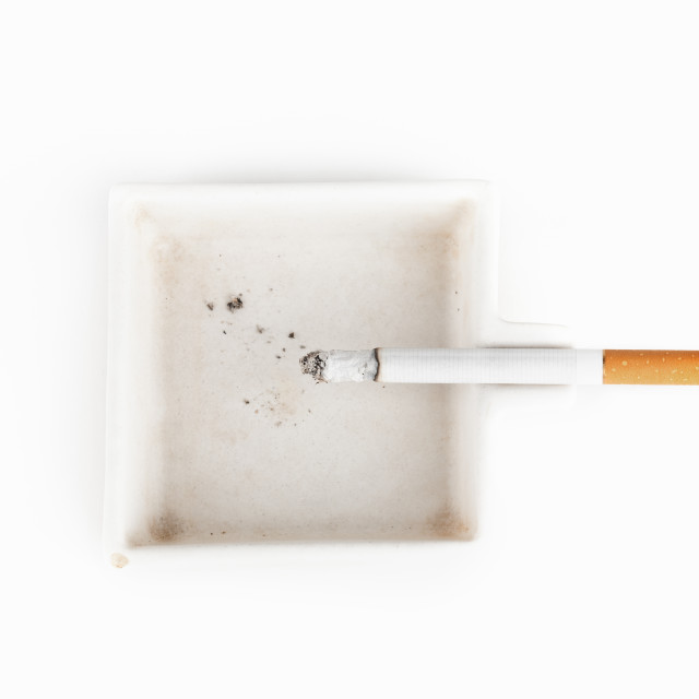 """""""A burning cigarette in a white ashtray studio isolated on white"""" stock image"""