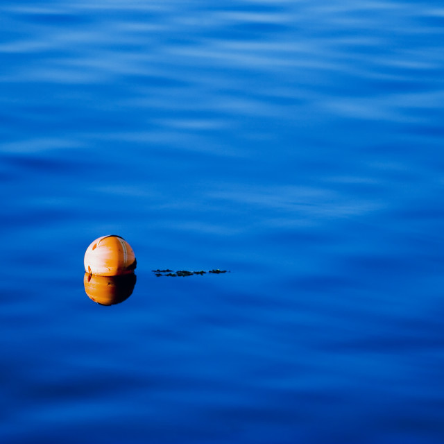 """Orange buoy on blue sea water"" stock image"