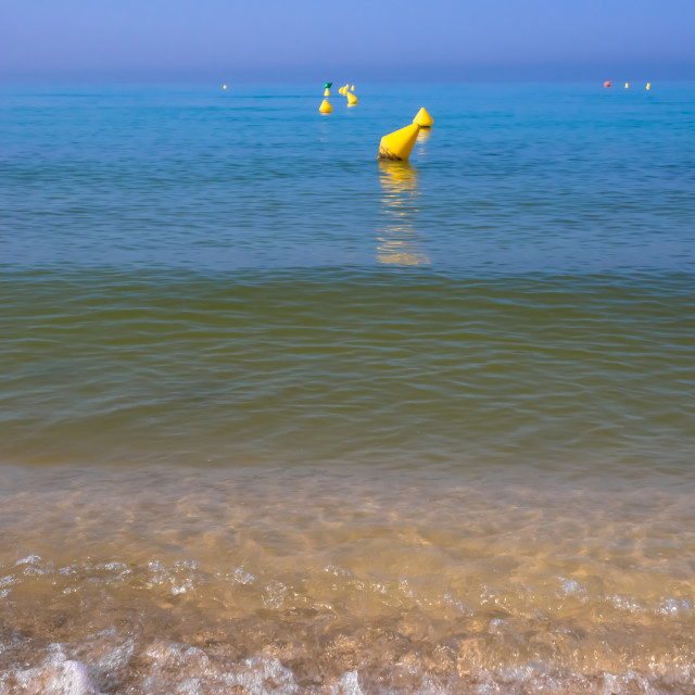 """Beach edge waves and buoys"" stock image"