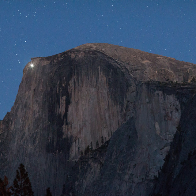 """A climber shines his light from just below the summit of Half Dome."" stock image"