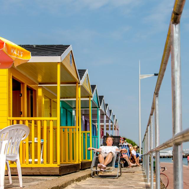"""Beach huts sunbathe"" stock image"