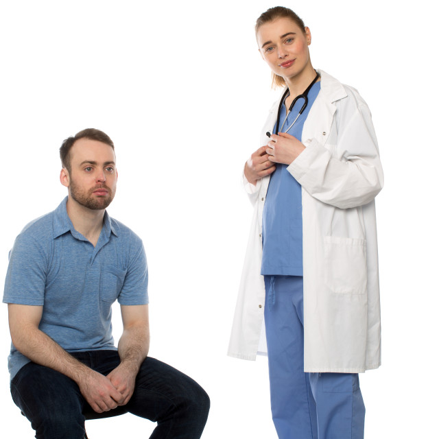 """Male Patient Sitting with Standing Female Doctor"" stock image"