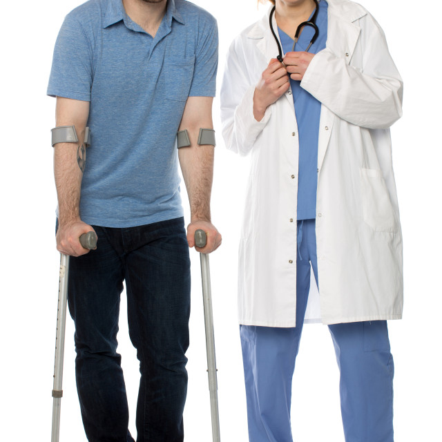 """Man using crutches, next to a friendly physician"" stock image"