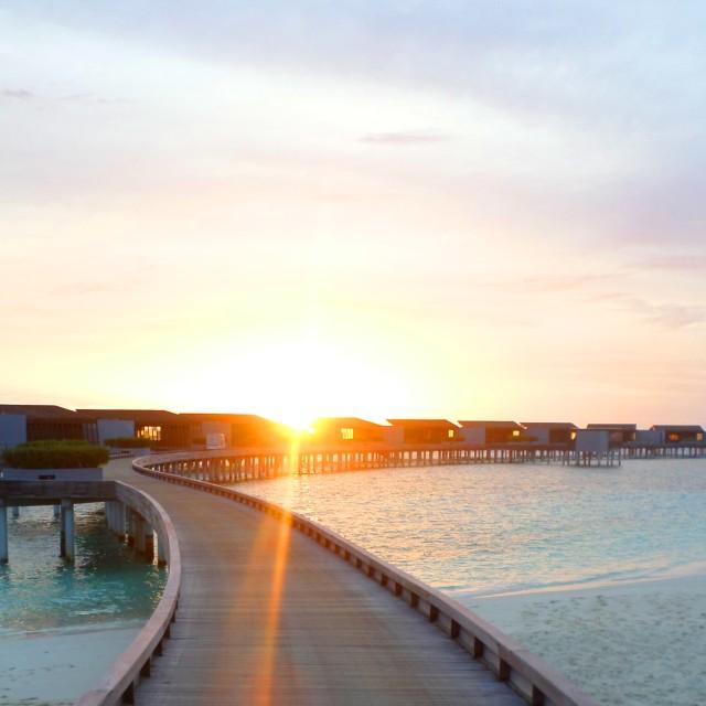 """Maldivian water villas at sunset"" stock image"