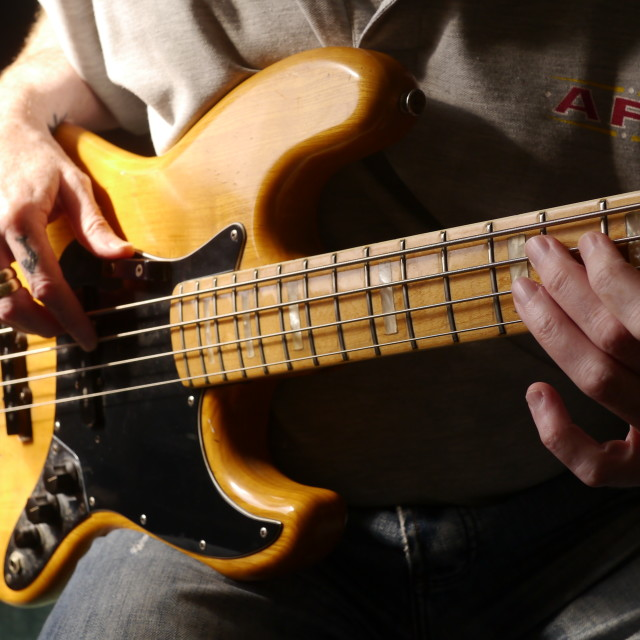 """Guitarist playing vintage Fender bass guitar"" stock image"