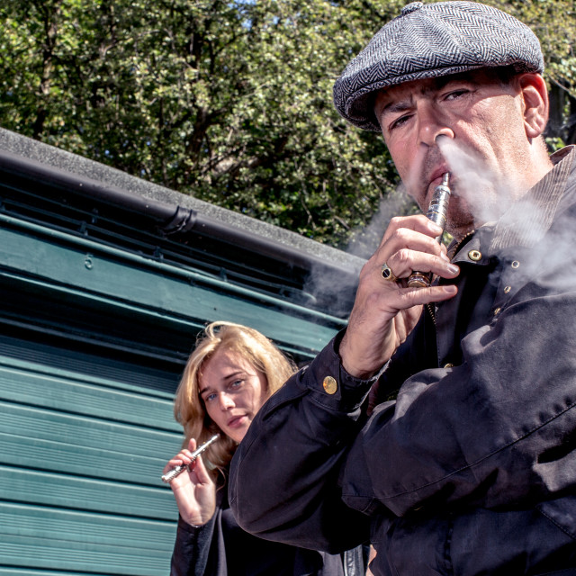 """Man and woman standing smoking e-cigarettes"" stock image"