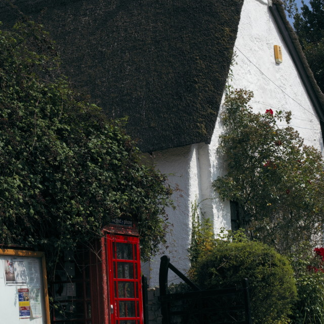 """""""Thatched cottage with red phone box."""" stock image"""
