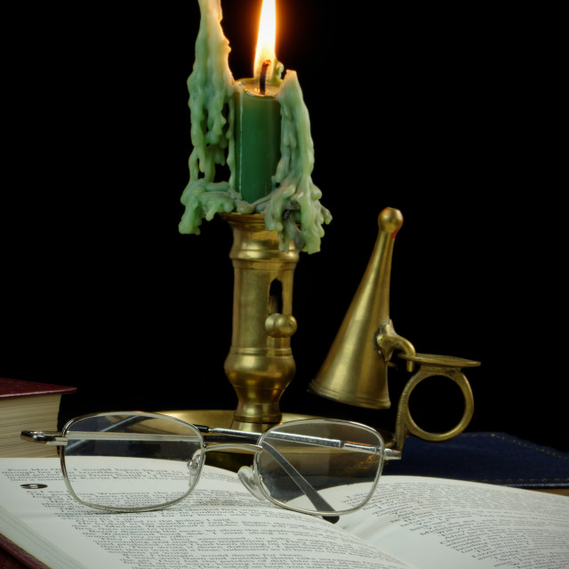 """Reading by candle light"" stock image"