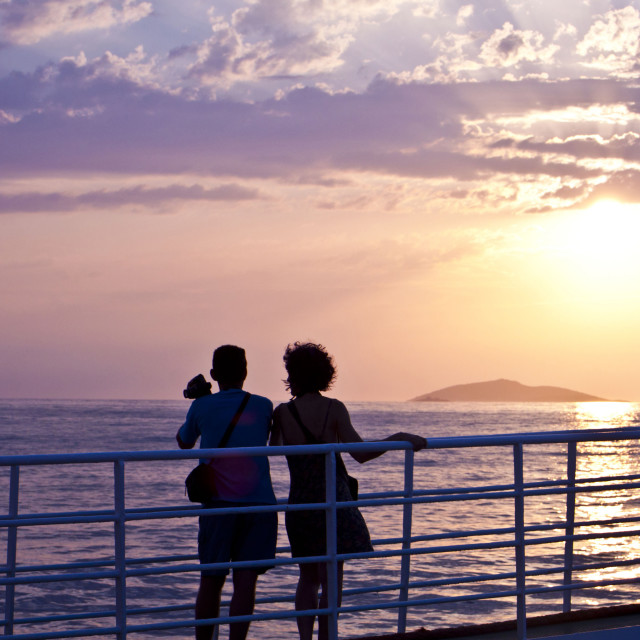 """Couple looking at sunset on sea and shooting pictures from ferry deck"" stock image"