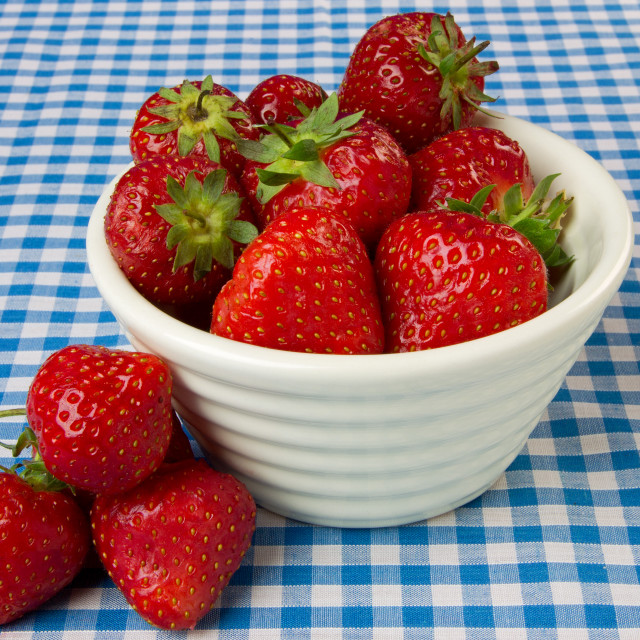 """Bowl of Strawberries on a Blue Gingham Tablecloth"" stock image"