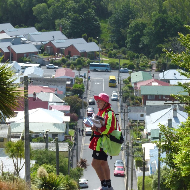 """Postman on steep street, NZ"" stock image"
