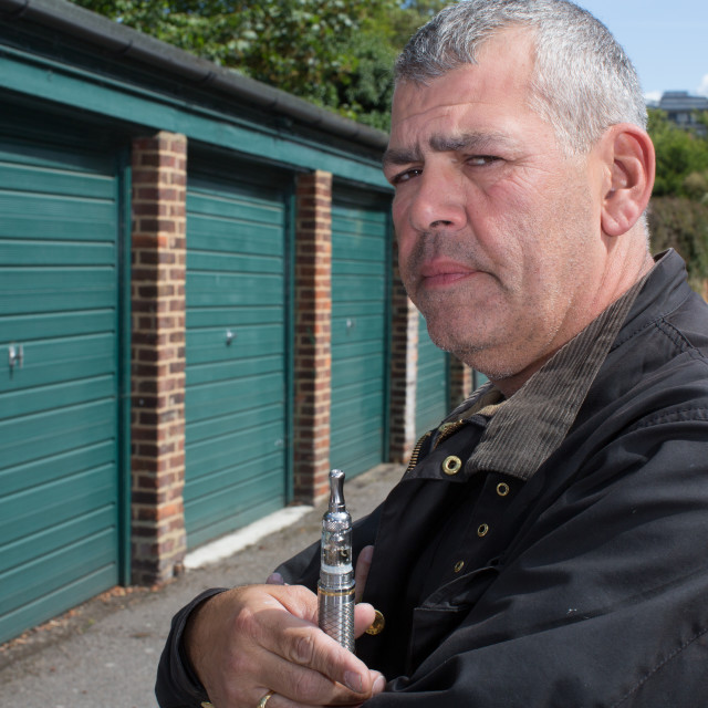 """""""Middle-aged man smoking an e-cigarette"""" stock image"""