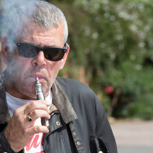 """""""Man in sunglasses puffing on an e-cigarette"""" stock image"""