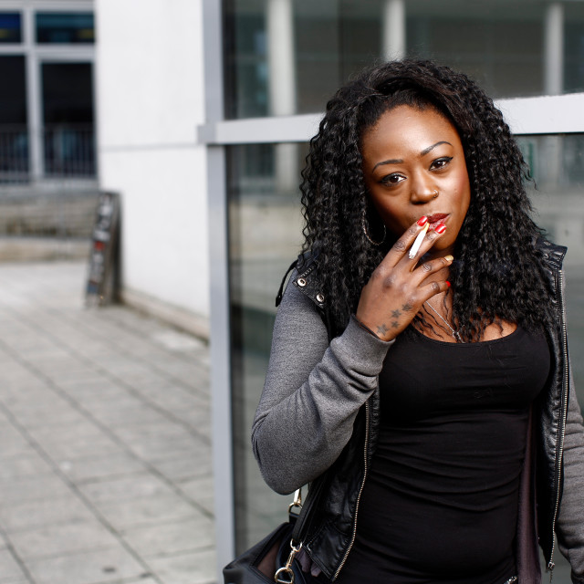 """""""Attractive young African-American woman smoking"""" stock image"""