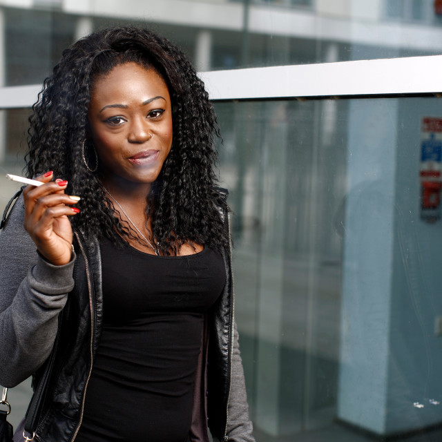 """""""Smiling African woman smoking a cigarette"""" stock image"""