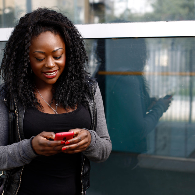 """""""Young African woman reading a text message"""" stock image"""