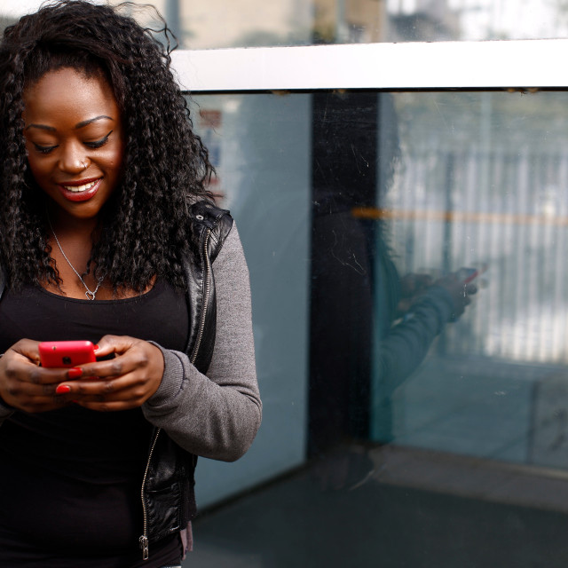 """Young African woman sending an sms on her mobile"" stock image"
