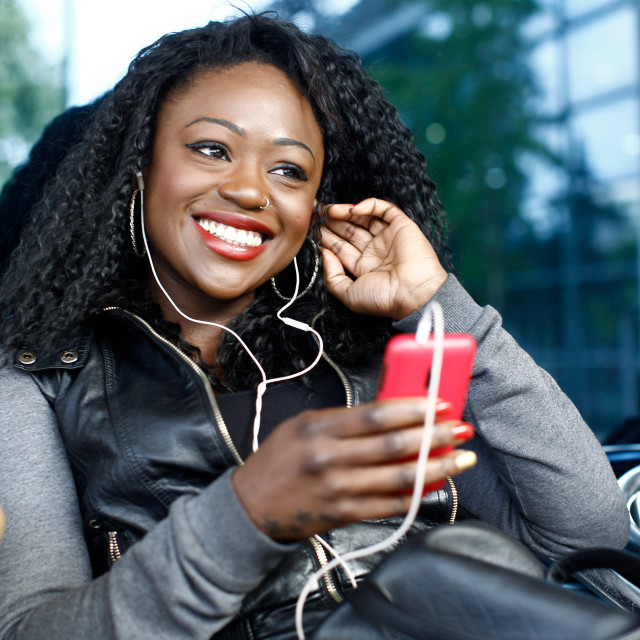 """""""African woman listening to music outdoors"""" stock image"""
