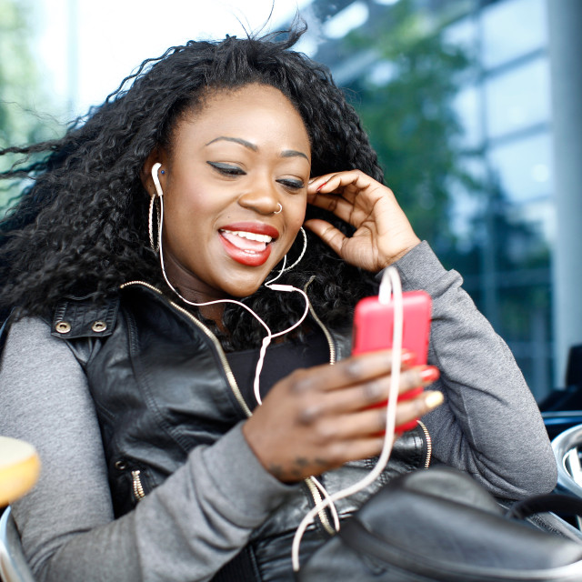 """""""Happy Woman Talking Through Phone and Headphone"""" stock image"""