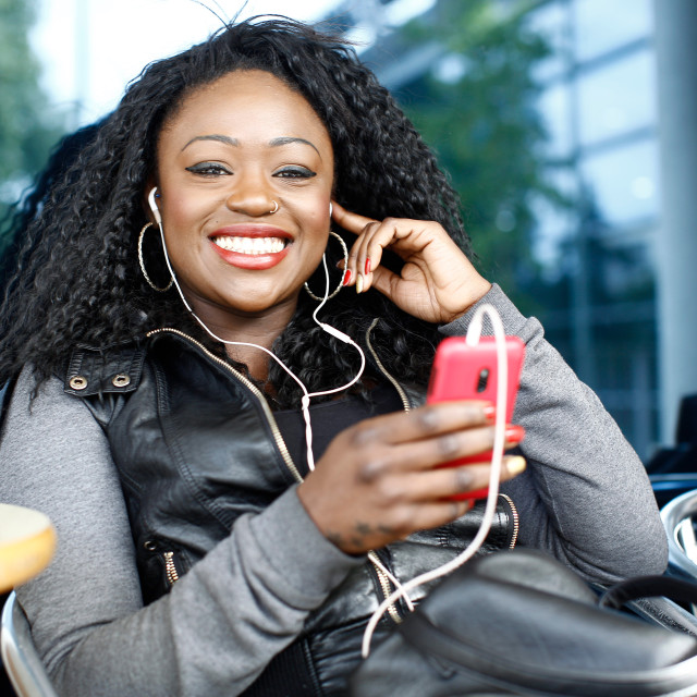 """""""Vivacious African woman listening to music"""" stock image"""