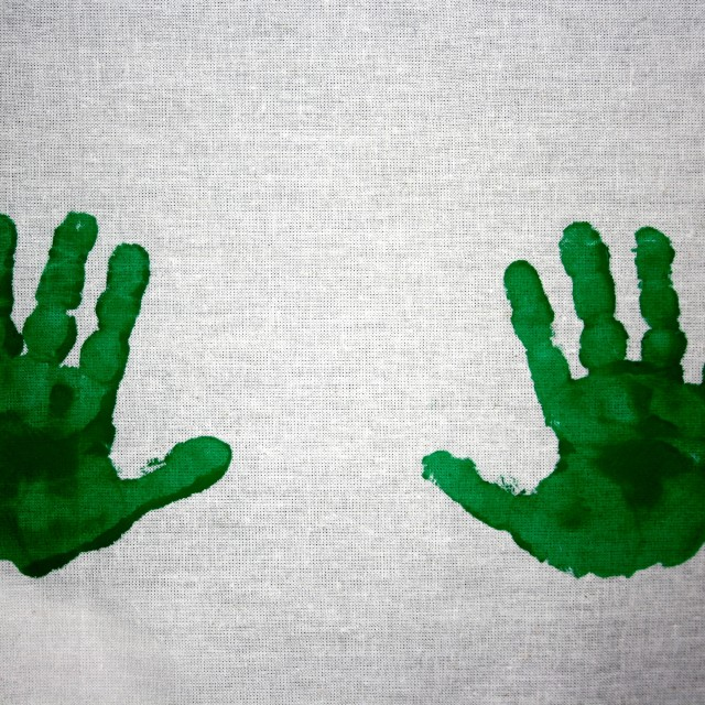 """Green handprints on white cotton"" stock image"