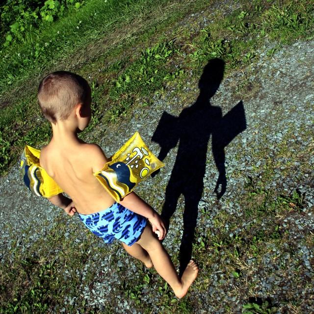 """Boy looking at shadow"" stock image"