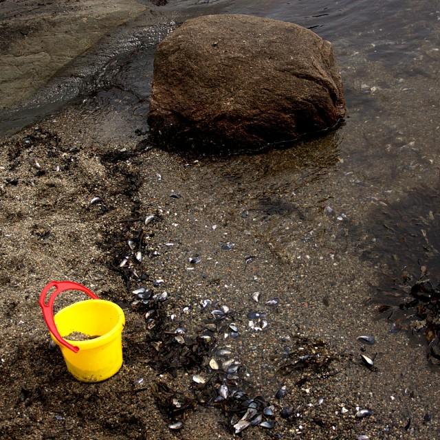 """Yellow bucket on the beach"" stock image"