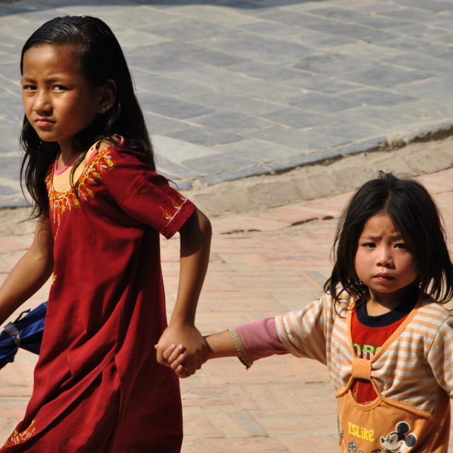 """Big sister taking care of her little sister at Bouddhanath Stupa"" stock image"
