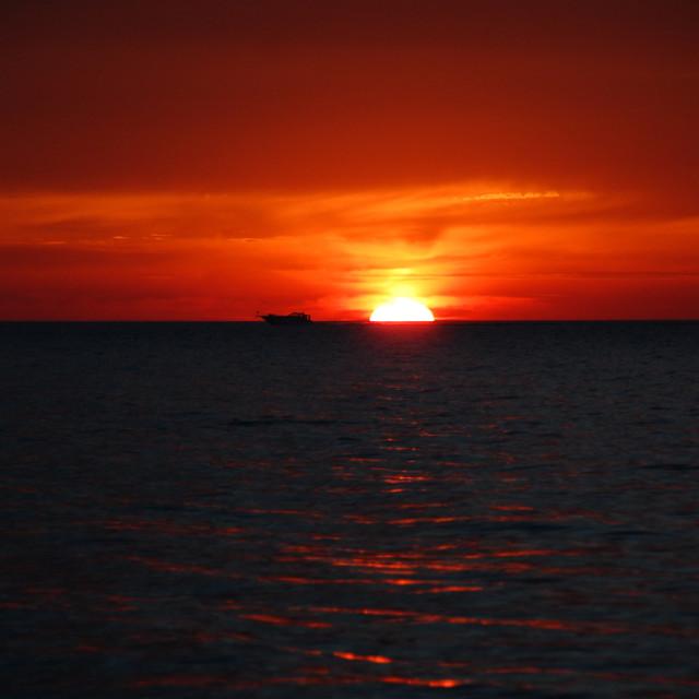"""""""Melting Sunset with drifting Boat"""" stock image"""