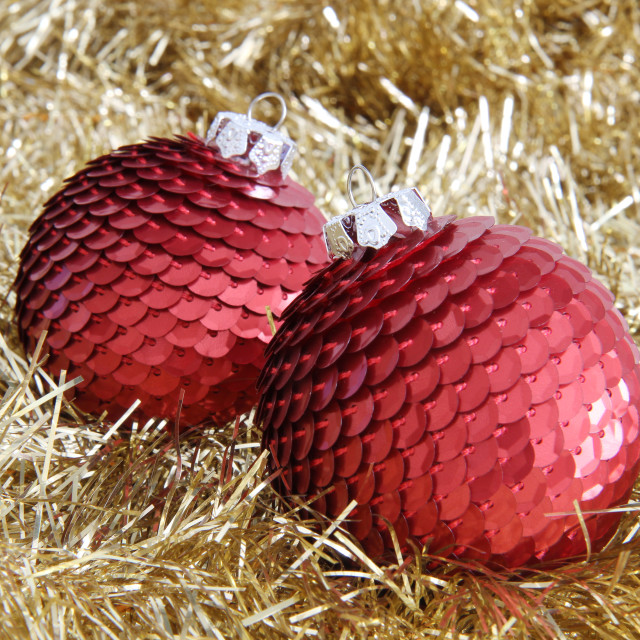 """Two red Christmas baubles on golden tinsel"" stock image"
