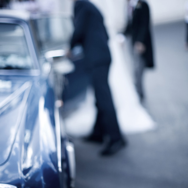 """Bride getting into vintage Rolls Royce wedding car"" stock image"