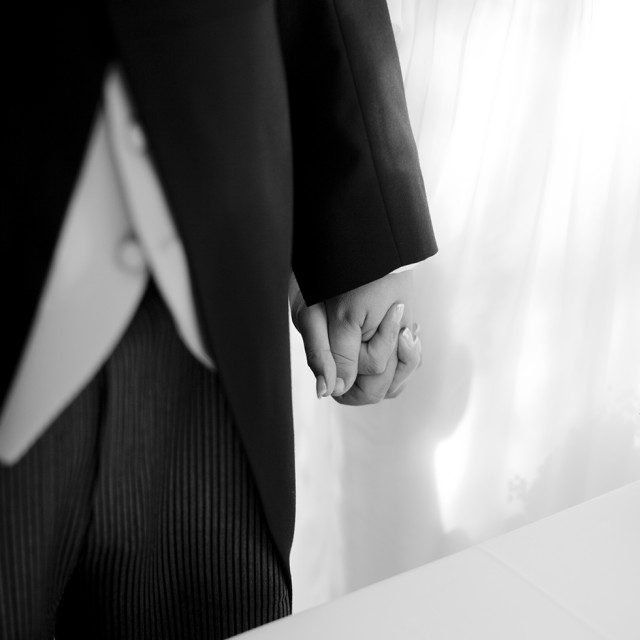 """Groom and bride in wedding marriage ceremony black and white holding hands"" stock image"