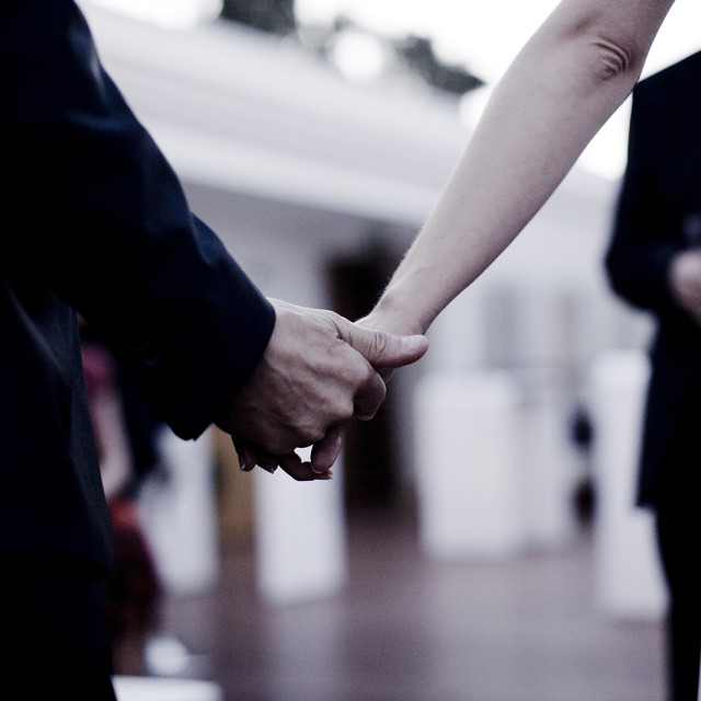 """Groom and bride in wedding holding hands in outdoor ceremony Spain"" stock image"