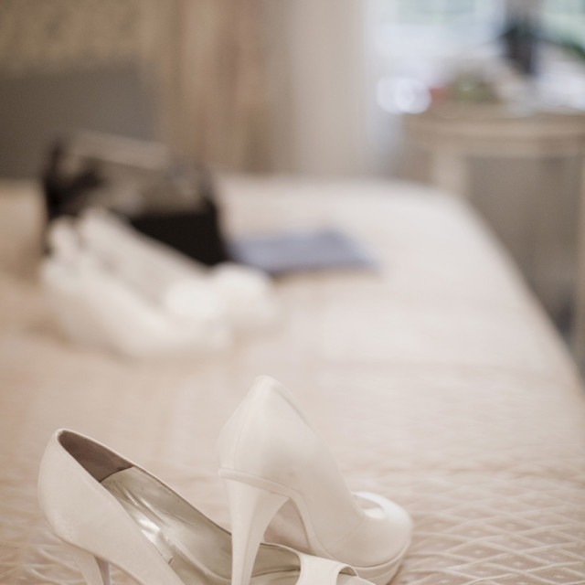 """""""White bridal shoes of bride on bed in bedroom still life marriage photo"""" stock image"""