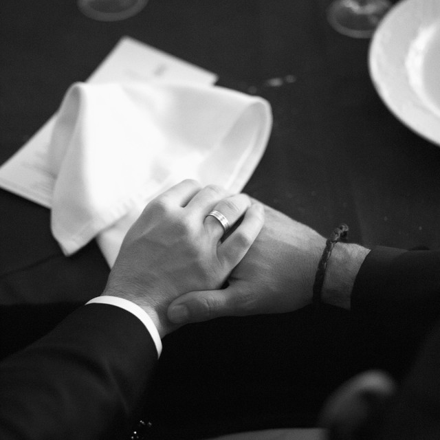 """Black and white groom and bride in wedding holding hands in marriage dinner"" stock image"