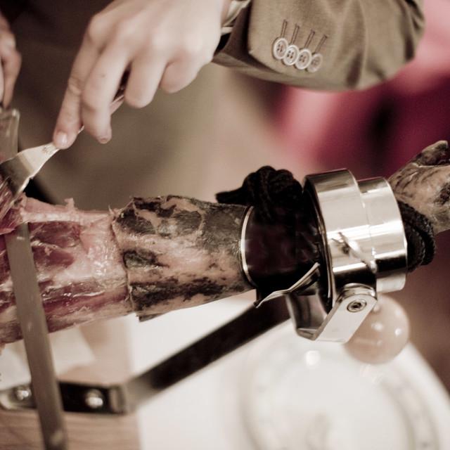 """Cutting leg of Iberian cured ham in Spanish wedding"" stock image"
