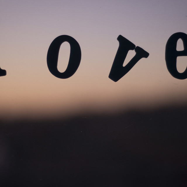 """""""Edward Olive Word love spelled in letters on window with sunset defocused"""" stock image"""