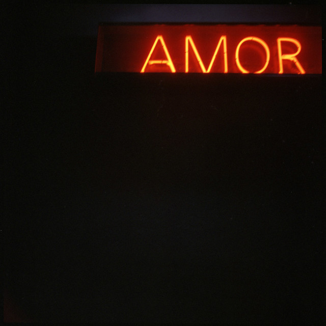 """""""Neon light sign """"amor"""" meaning love in Spanish on black background"""" stock image"""