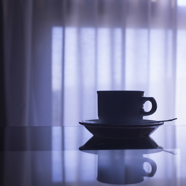 """Tea or coffee cup and saucer on table in room stock photograph"" stock image"