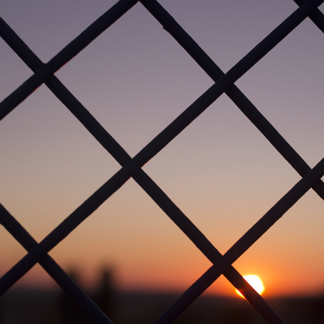 """""""Sunset sun and blue dusk sky and wire mesh fence fair deal photo stock"""" stock image"""