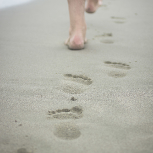 """Feet of man and footprints on sand of beach color digital photo"" stock image"