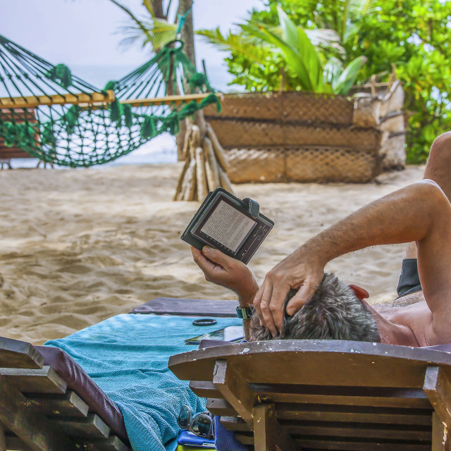 """Reading an e book on the beach"" stock image"