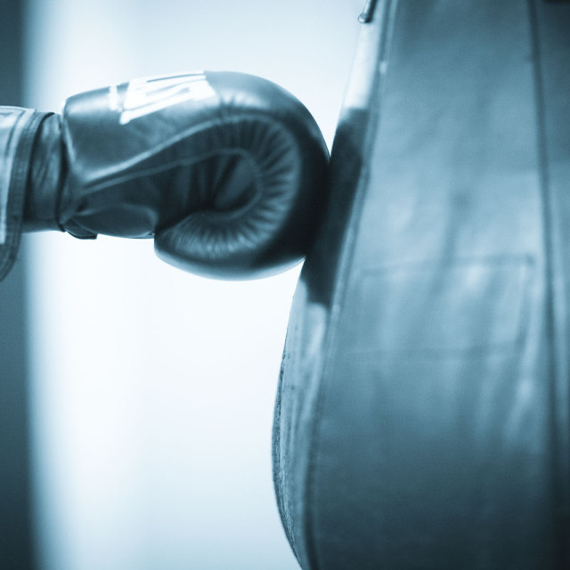 """""""Everlast boxing glove of boxer hitting punch bag in gym training"""" stock image"""