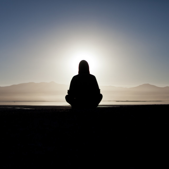 """Meditating at Sunrise in the Atacama Desert, Bolivia"" stock image"